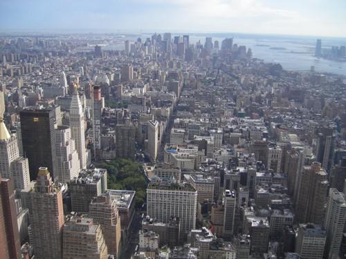 На юг от Емпайър Стейт Билдинг / горе, в дясната страна  на снимката,  е островът със Статуята на свободата, а зад него – Елис Айлънд /