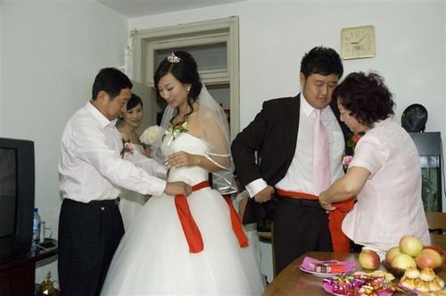 Родителите връзват червени пояси на младоженците за щастие