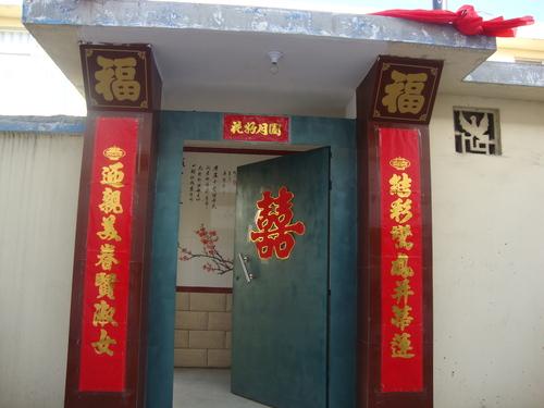 Портата към дома на Лианг, украсена с пожелания