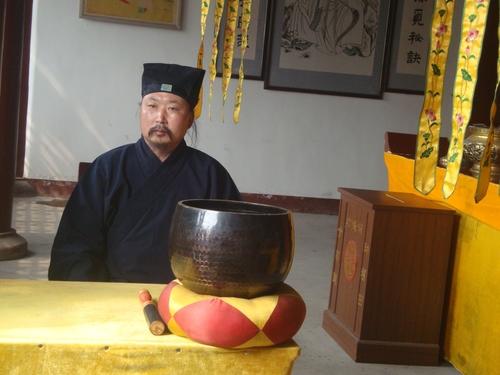 Таоистки монах - купата пред него служи за камбана