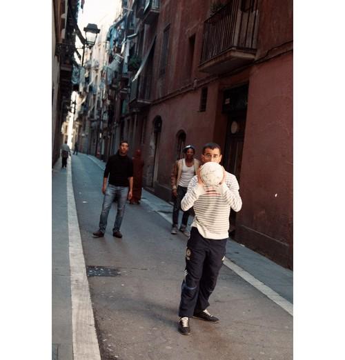 Момчета играят футбол на улица в Барселона.