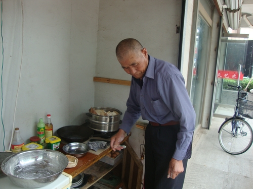 Мъж си готви пред магазина