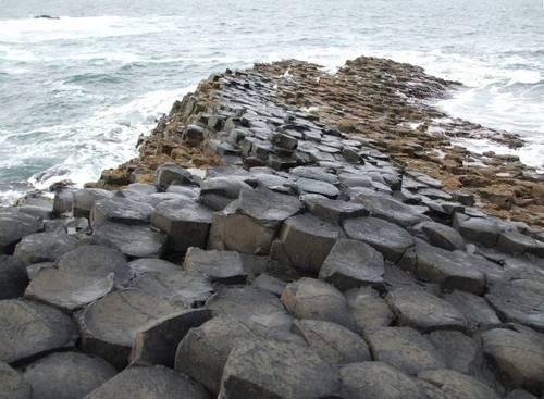 Каменният хълм се спуска към океана и продължава под водата