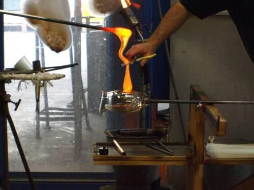 Дръжката на каната се оформя като разтопената стъклена маса провисва, а вторият работник я отрязва с ножица. След това, той чрез ловко завъртане оформя дръжката и я залепва за корпуса на каната.
