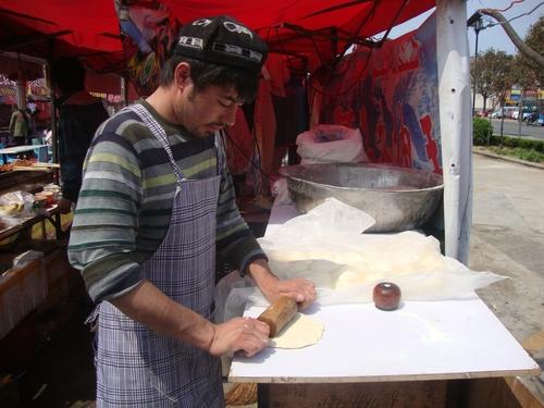 младеж от Син дзиан разточва тесто за питки,