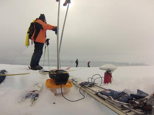GPS приемник в режим на статично измерване върху дървен репер в ледника Перуника, в дъното - залива Емона. На снимката – Цецо (преден план), Божо и Васил