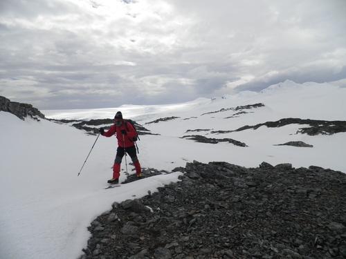 Остров Ливингстън и полярният изследовател Васил Гурев, в дъното – планините Боулс и връх Бърдик (773 m)