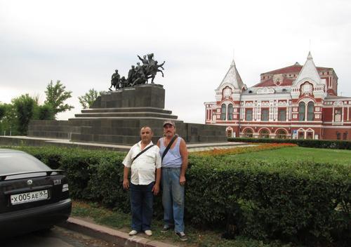 Двамата строители от Узбекистан на фона на паметника на Чапаев и Драматичния театър