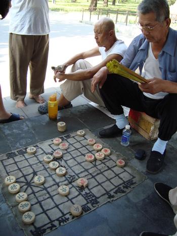 мъже играят китайски шах под навеса